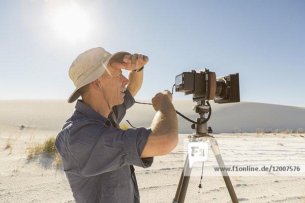 Caucasian photographer with tripod shielding eyes in desert