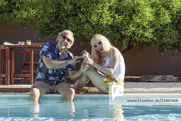 Caucasian couple smiling near swimming pool