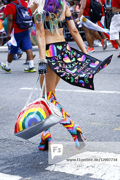 Person wearing high heel boots carrying purse in pride parade