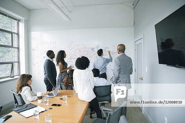 Businessman writing on whiteboard in meeting