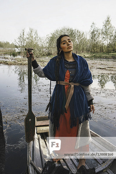 Caucasian woman wearing traditional clothing in rowboat