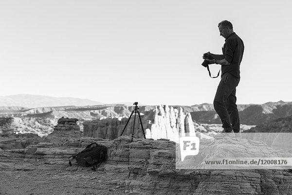 Caucasian photographer with tripod in desert