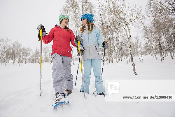 Caucasian mother and daughter snowshoeing