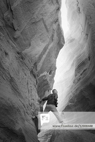 Caucasian man climbing rock formation