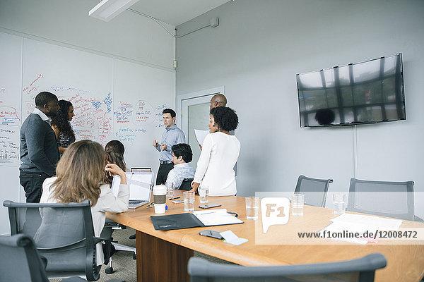 Businessman talking near whiteboard in meeting