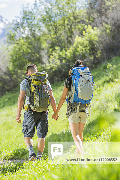 Couple carrying backpacks hiking on hill