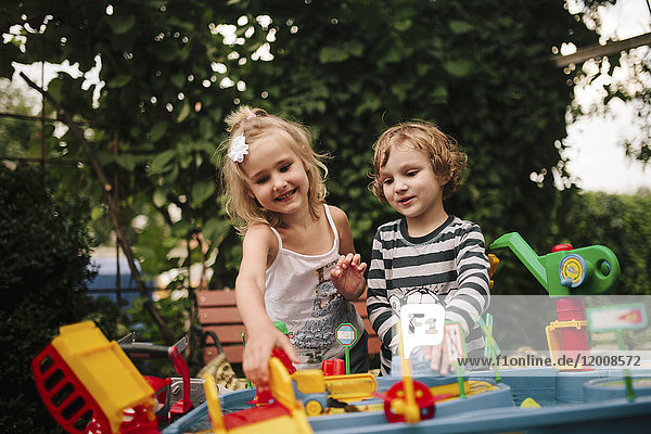 Caucasian boy and girl playing with toys outdoors