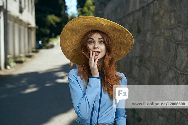 Surprised Caucasian woman wearing hat near stone wall