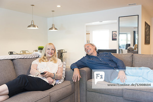 Caucasian couple watching television in livingroom