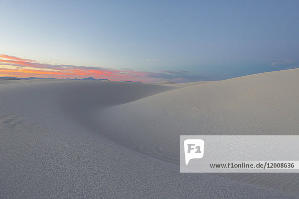 Sand dunes in desert at sunset