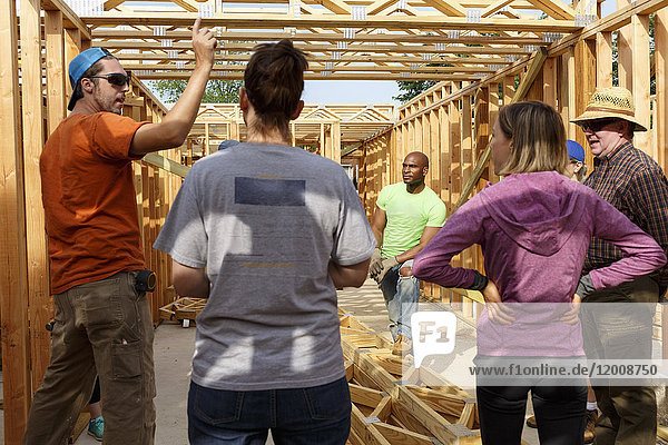 Volunteers talking while building a house