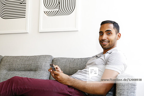 Mixed race man sitting on sofa texting on cell phone