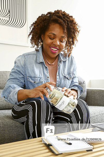 Mixed race woman screw lid on jar of money for college