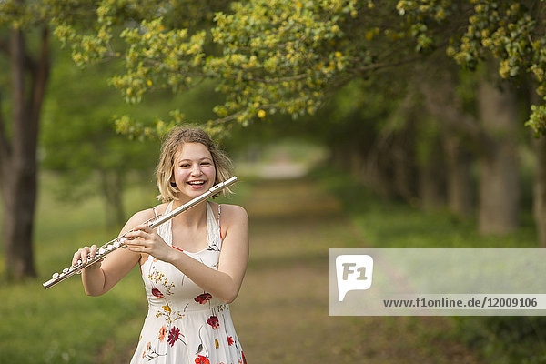 Caucasian teenage girl playing flute in park