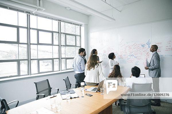 Business people talking near whiteboard in meeting