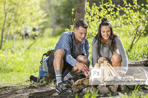 Couple building campfire in the woods