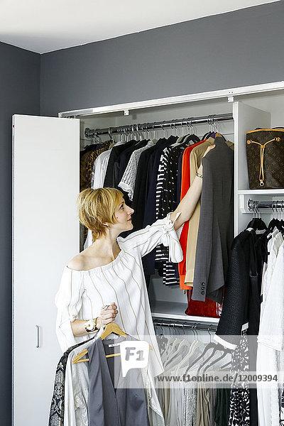 Caucasian woman holding clothing near closet