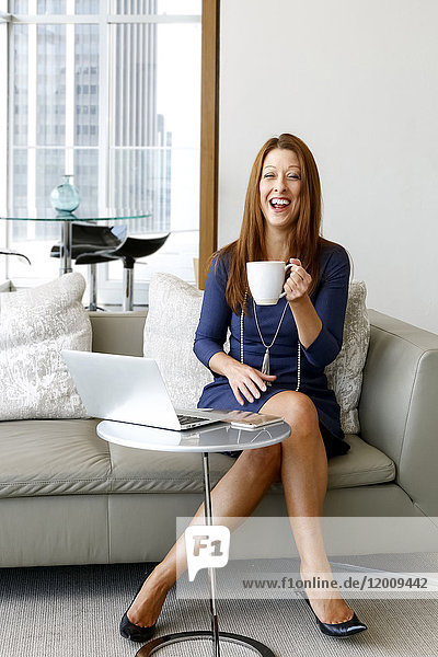 Caucasian businesswoman drinking coffee and laughing