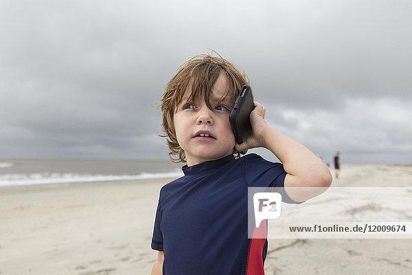 Caucasian boy talking on cell phone on beach