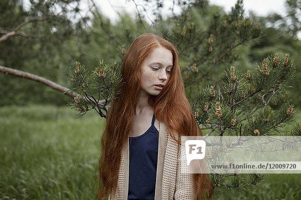 Caucasian girl standing near tree branch