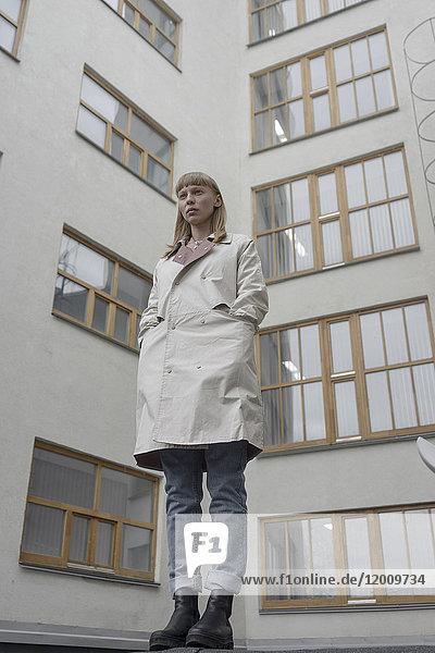 Caucasian woman wearing a coat near building