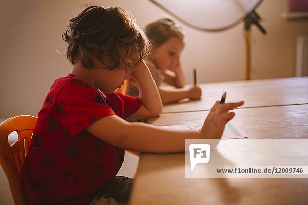 Caucasian boy and girl sitting at table with pencil and paper