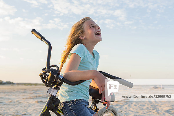 Laughing Caucasian girl leaning on bicycle at beach