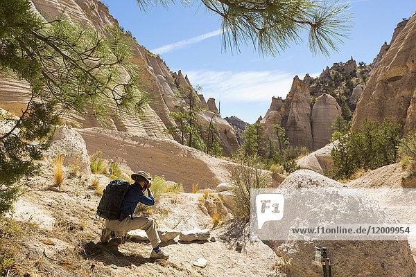 Caucasian man photographing desert landscape