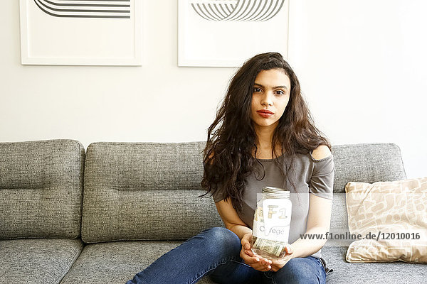 Portrait of mixed race woman holding jar of money for college