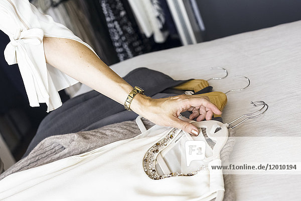 Arm of Caucasian woman placing clothing on bed