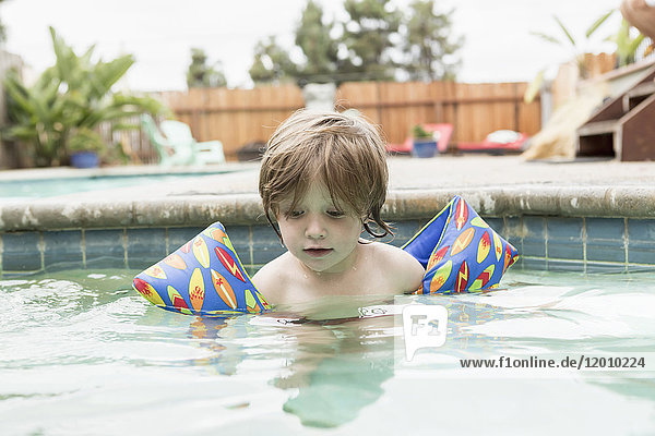 Caucasian boy wearing water wings in swimming pool