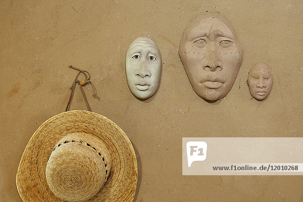 Clay masks and hat hanging on wall