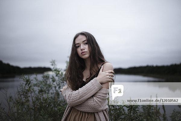 Portrait of serious Caucasian woman standing near a river