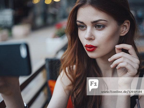 Smiling Caucasian woman posing for cell phone selfie