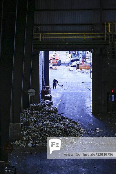 Man sweeping garbage with broom