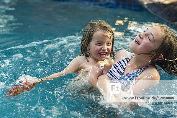 Caucasian brother and sister playing in swimming pool