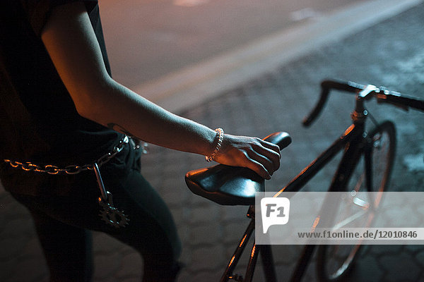 Caucasian man holding a bicycle seat at night