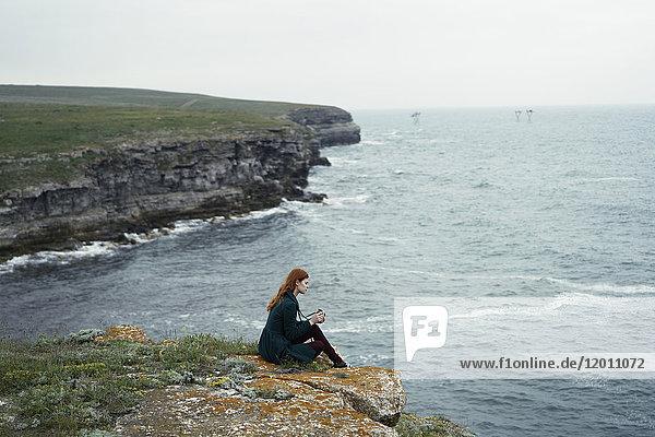 Caucasian woman examining camera near ocean