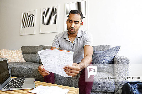 Mixed race man sitting on sofa reading paperwork