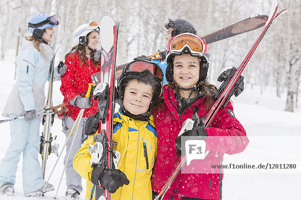 Portrait of smiling Caucasian brother and sister carrying skis