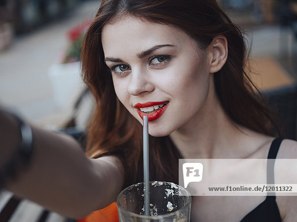 Smiling Caucasian woman drinking from straw posing for selfie