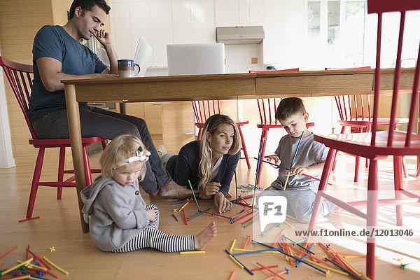 Vater arbeitet am Laptop am Tisch und Mutter mit Kleinkindern, die mit Steckern am Boden spielen.