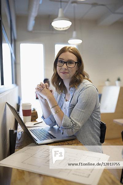 Portrait selbstbewusste Architektin mit Blaupausen am Laptop im Büro