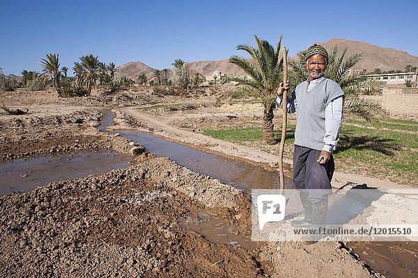 Man managing the arrival of water in an oasis  Garmeh  Iran