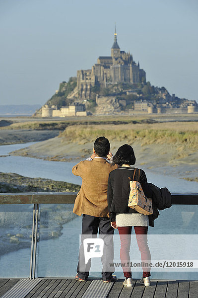 France  Lower Normandy Region  Manche Department  Mont St-Michel seen from the dam on Couesnon river  couple of Asian visitors taking a picture.
