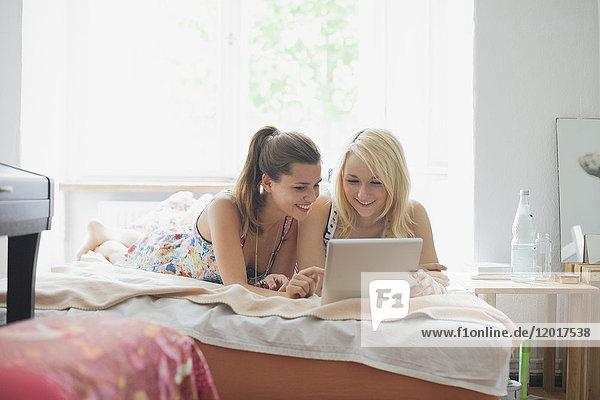 Lächelnde  schöne  junge Freundinnen  die zu Hause auf dem Bett liegend ein digitales Tablett benutzen.