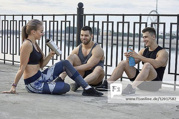 Junge Athleten  die sich auf dem Fußweg mit dem Geländer ausruhen