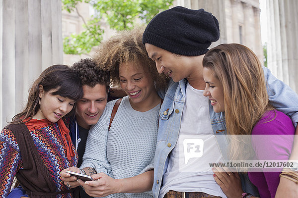 Young woman showing mobile phone to friends