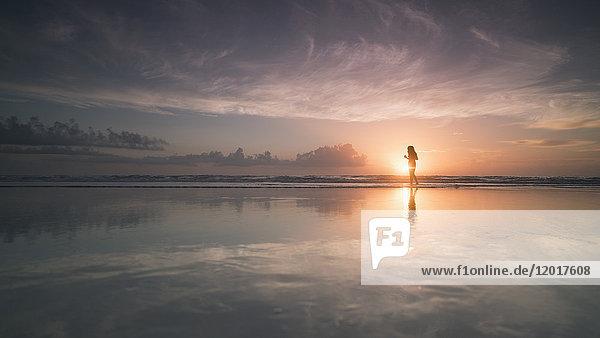 Silhouette Frau am Meeresufer gegen bewölkten Himmel bei Sonnenuntergang  Daytona  Florida  USA Silhouette Frau am Meeresufer gegen bewölkten Himmel bei Sonnenuntergang, Daytona, Florida, USA