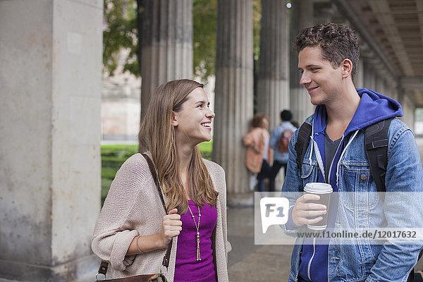 Lächelnde junge Freunde beim Reden gegen die Säulen